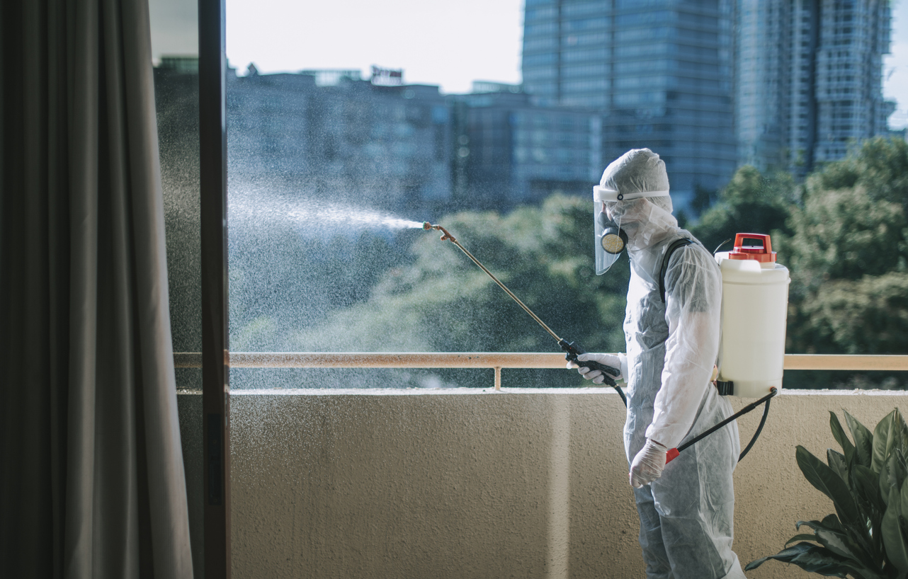 Oneman in protective suit spraying the house and disinfecting the housing exterminator pest control virus